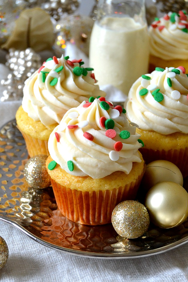 Three eggnog cupcakes on a silver platter with gold ornaments