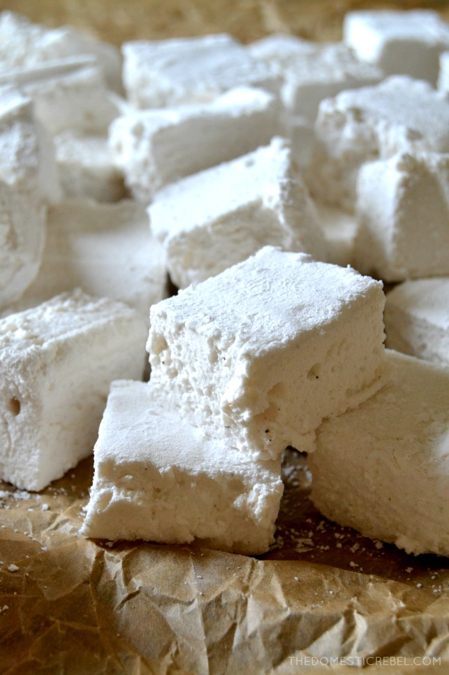 Many homemade marshmallows lying in a pile on brown parchment paper
