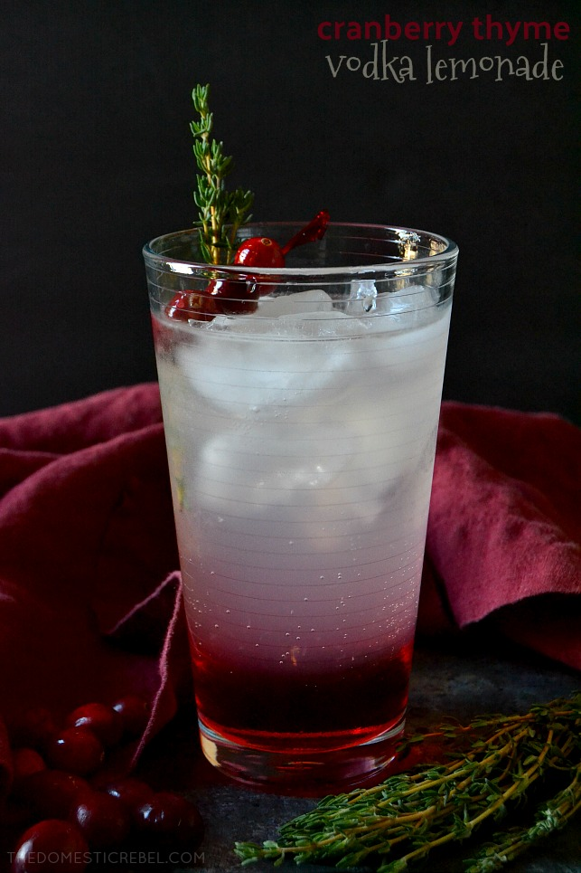 cranberry thyme vodka lemonade on dark background with fresh cranberries and thyme sprigs