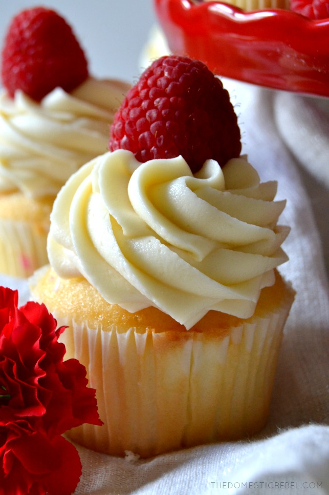 These White Chocolate Raspberry Cupcakes are moist, tender vanilla cupcakes filled with a tart and tangy raspberry jam and topped with a silky mountain of white chocolate buttercream! Sweet, creamy, soft and delicious!