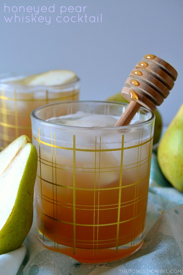 honeyed pear whiskey cocktail with honey dipper and pears