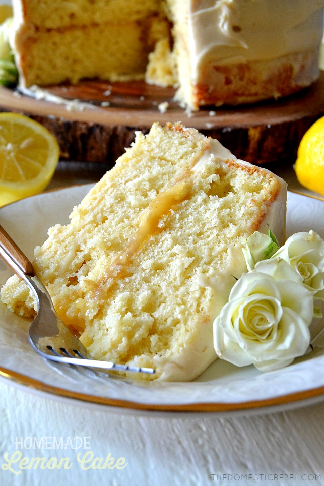 homemade lemon cake slice on white plate with white roses and fork