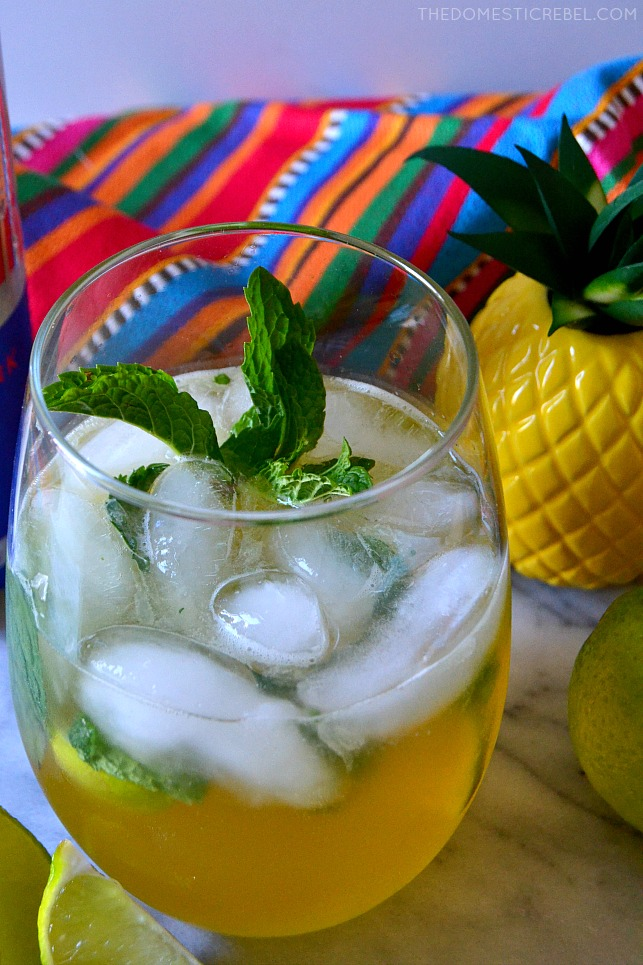 closeup of red bull pina cocojito in glass with pineapple figurine and lime wedges