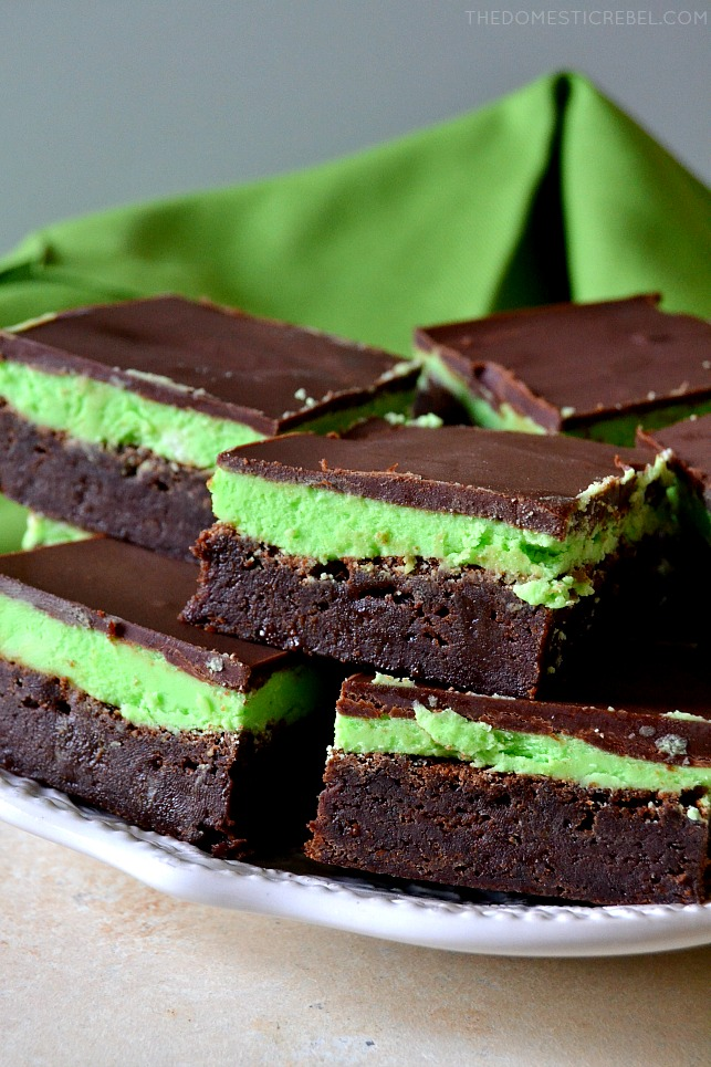 mint chocolate brownies stacked on white plate with green fabric