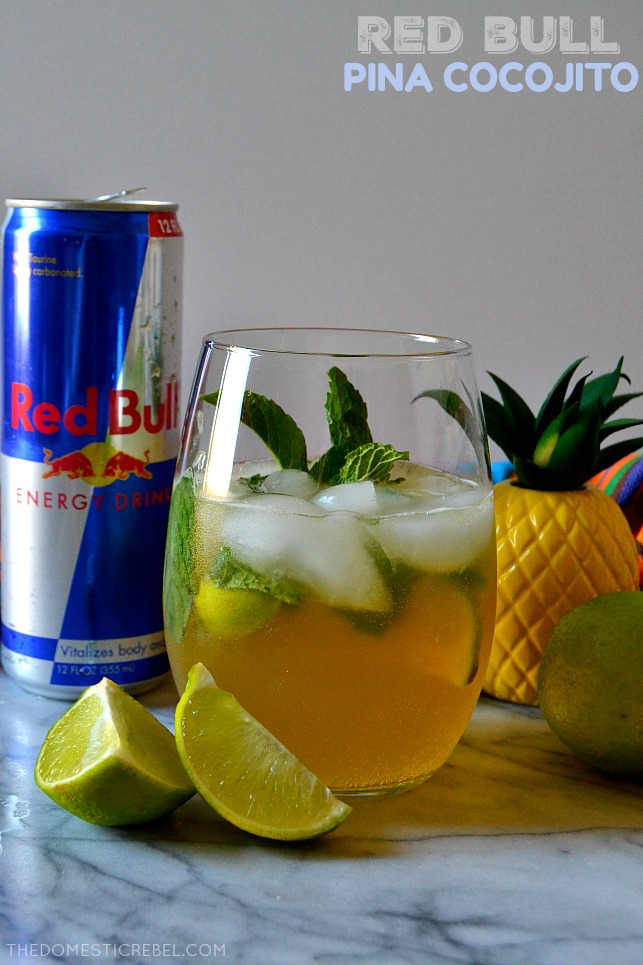 red bull pina cocojito drink in glass with red bull can and lime wedges