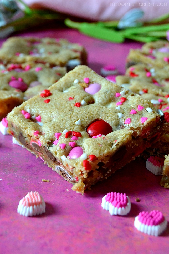 valentine m&m cookie bar on pink wood with heart candies