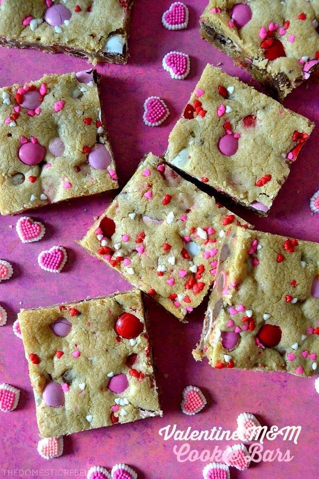 valentine M&M cookie bars arranged with candies on pink background