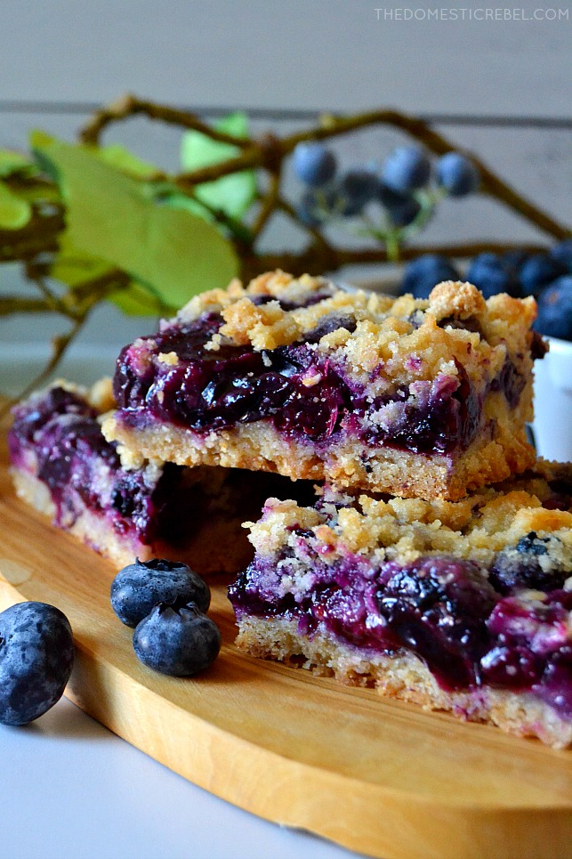 Blueberry Crumb Bars arranged on wood plank with fresh blueberries