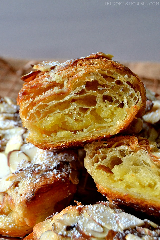 closeup of split open almond croissant in a pile