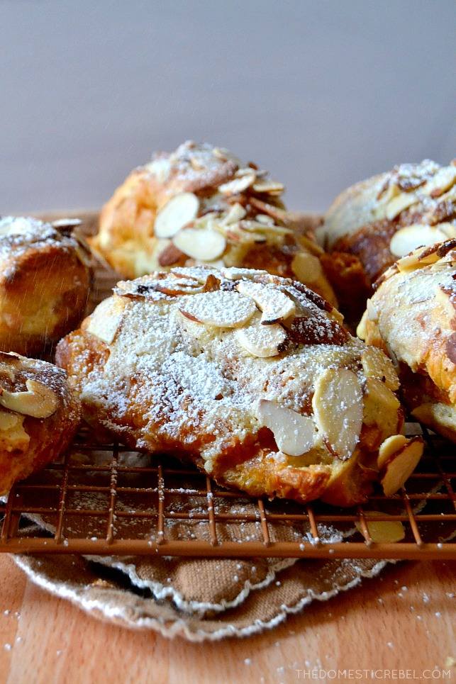 almond croissants arranged in rows on wire rack