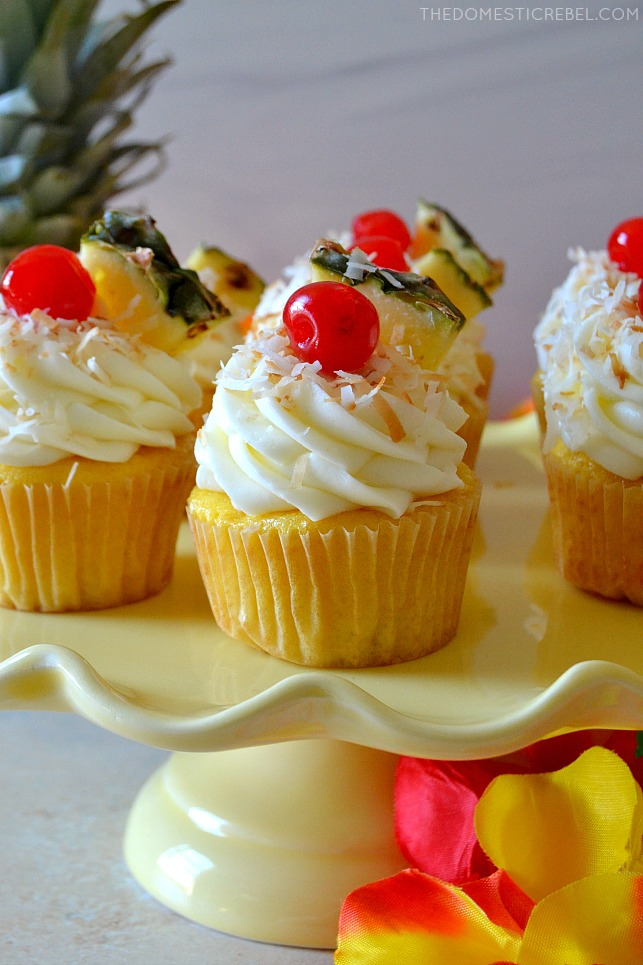 pina colada cupcakes on yellow cake stand with flowers