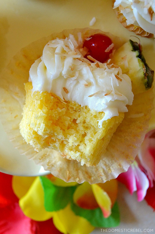 pina colada cupcake with bite missing on yellow stand