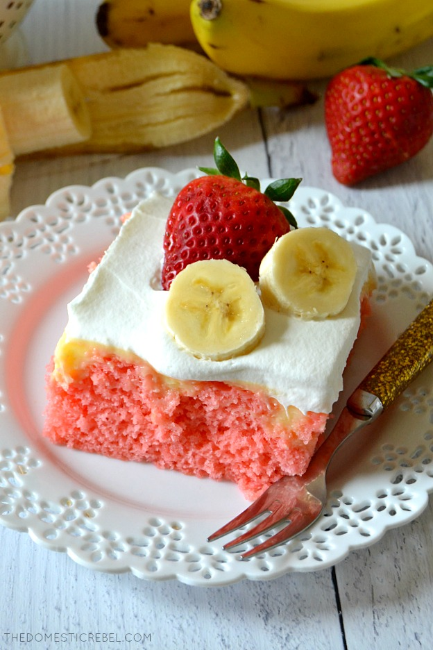 strawberry banana poke cake on white plate with fork and a strawberry and banana in background