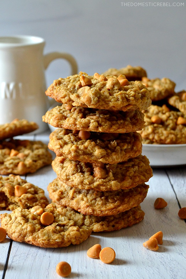 oatmeal scotchie cookies stacked high on wood with butterscotch chips