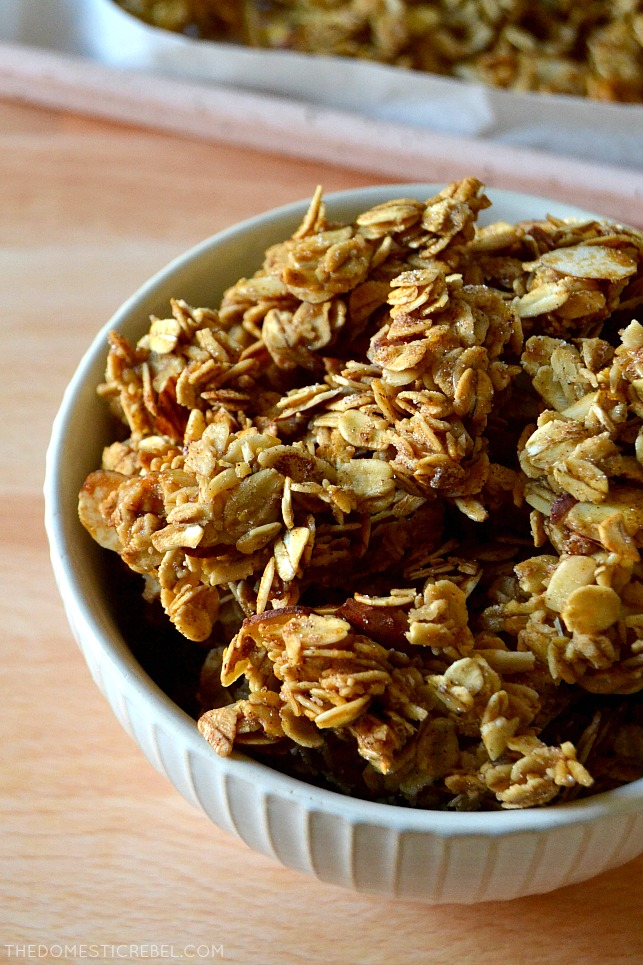 granola clusters in white bowl on wood