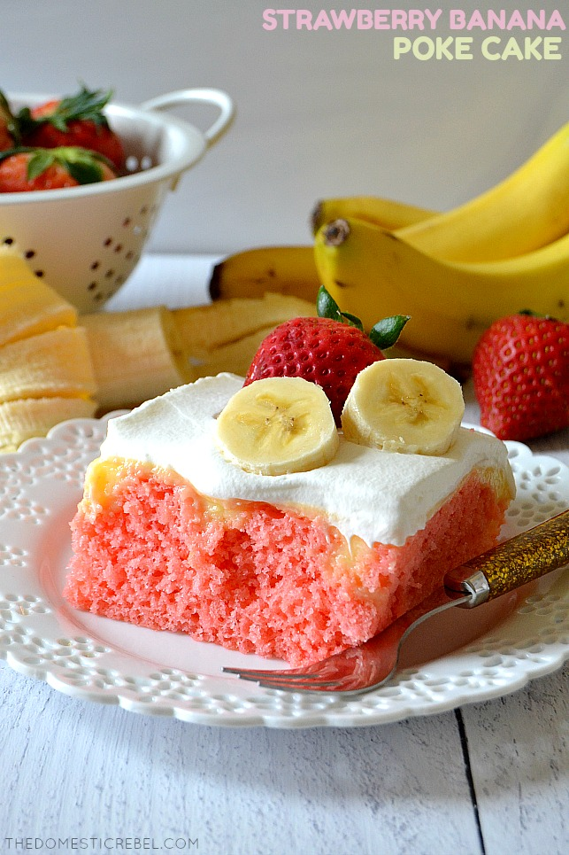 strawberry banana poke cake on white plate with fork and fresh fruit in background