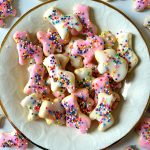 a plate of frosted circus animal cookies on a marble background