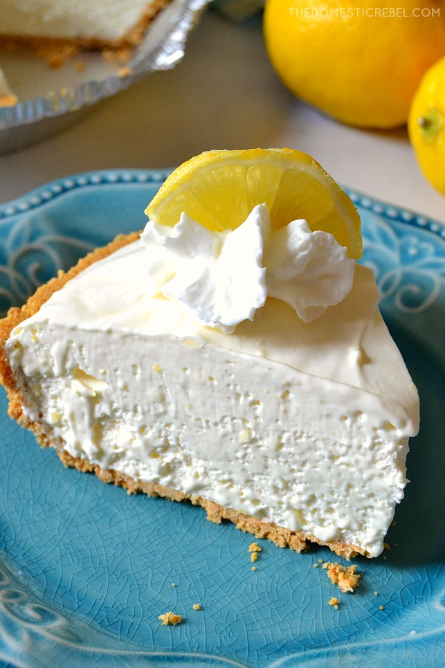 Closeup of slice of Lemonade Pie on blue plate with a lemon in background