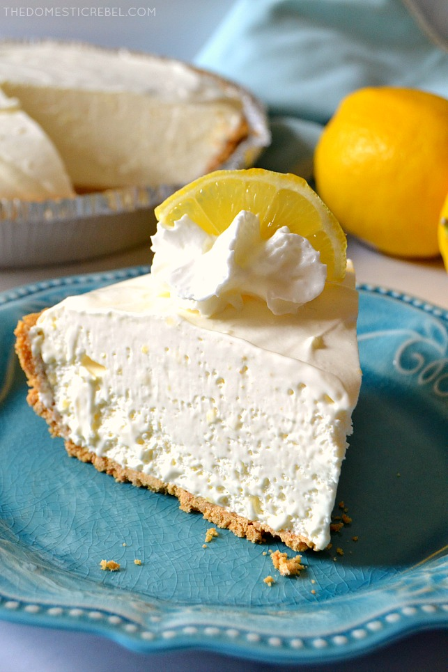 Closeup of Frozen Lemonade Pie slice on blue plate with pie and lemons in background