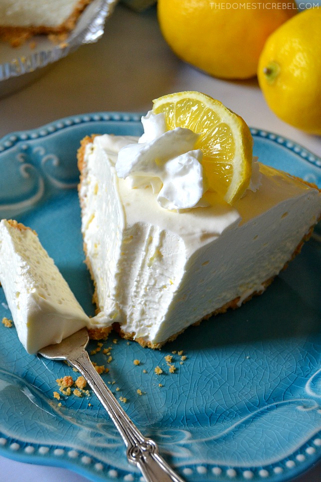 Frozen Lemonade Pie slice on blue plate with fork and lemons in background