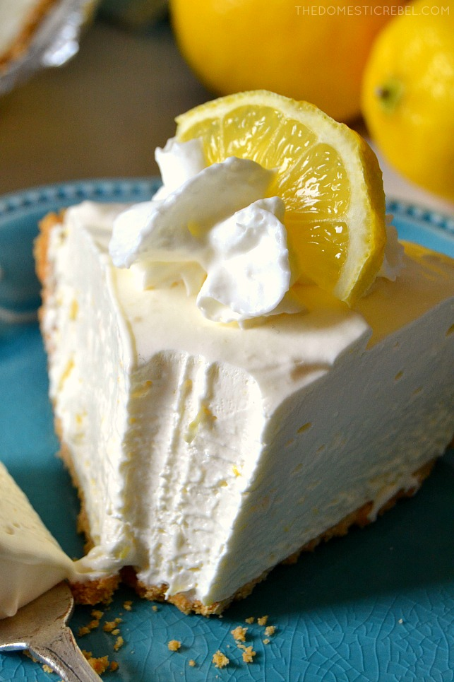 Frozen Lemonade Pie on blue plate with lemons in background