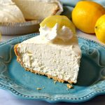 Frozen Lemonade Pie slice on blue plate with lemons