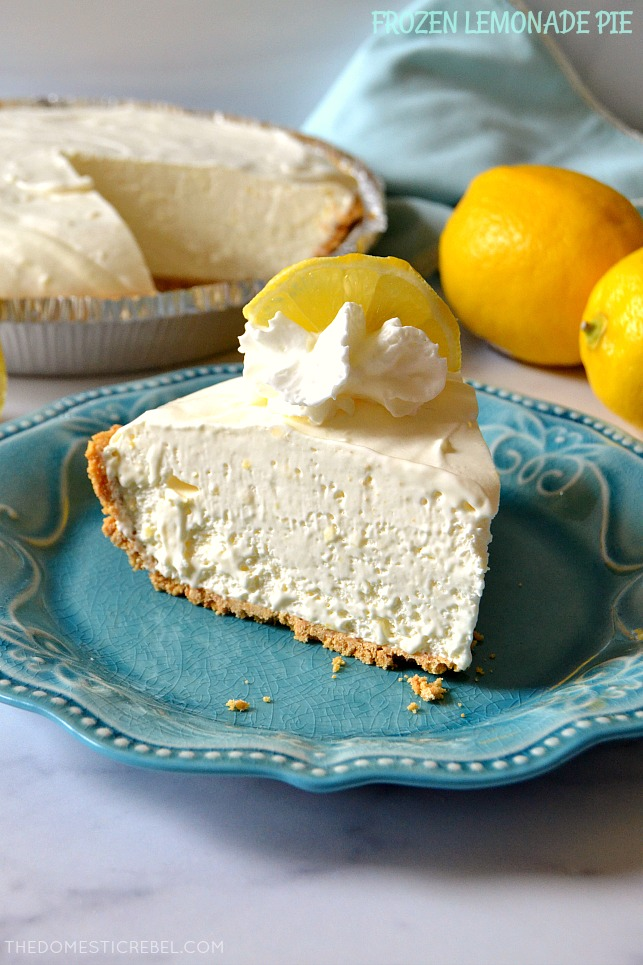 Frozen Lemonade Pie slice on blue plate with lemons and a whole pie in background