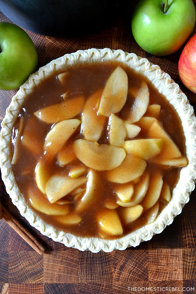 Apple pie filling in an unbaked pie crust on wooden background with apples