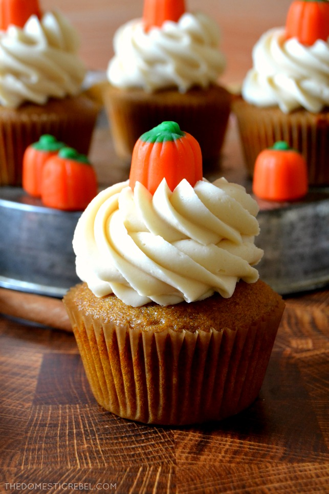 Pumpkin cupcake on wooden board with cupcakes in background