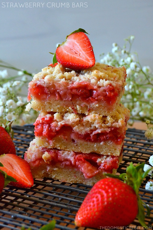 trio of strawberry crumble bars on a wire rack with berries and flowers