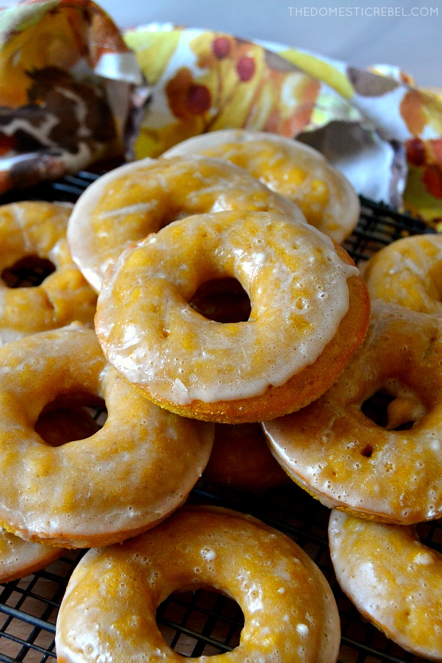pumpkin cake donuts stacked on a wire rack with a dish towel