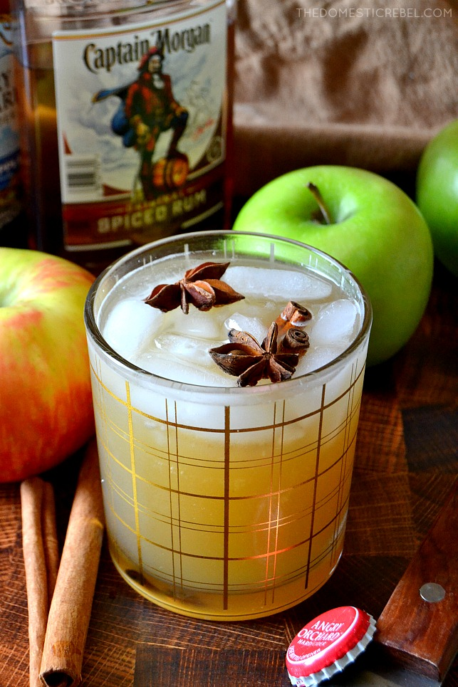 Apple Cider Spiced Rum Cocktail on wood background with rum and apples in background