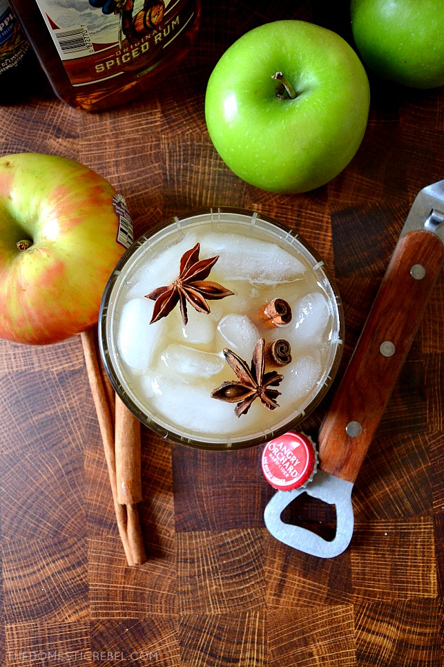 Aerial shot of apple cider cocktail on wood background with apples