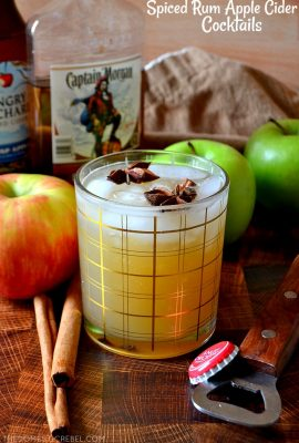 Spiced Rum Apple Cider Cocktail with apples and cinnamon sticks