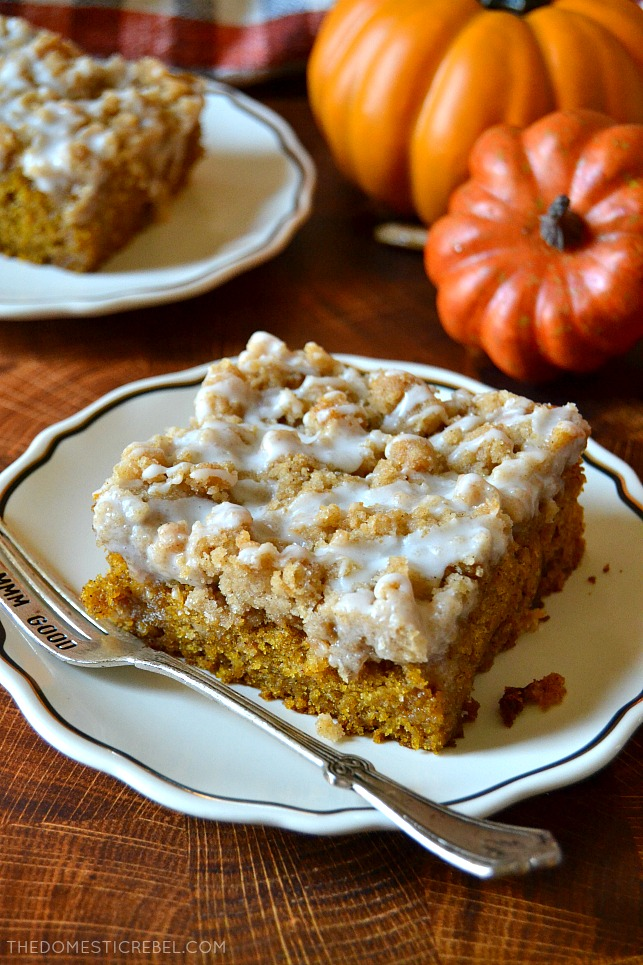 Photo of a piece of pumpkin spice coffee cake on a wooden board with faux pumpkins in background