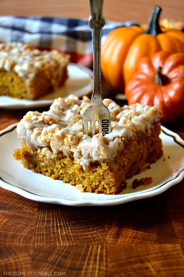 A piece of pumpkin spice coffee cake on a white plate with a fork stuck in it.