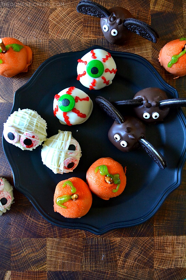 An assortment of Halloween oreo balls on a black plate