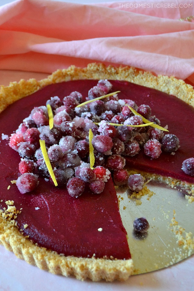 A cranberry lemon tart on a pie pan with a pink towel