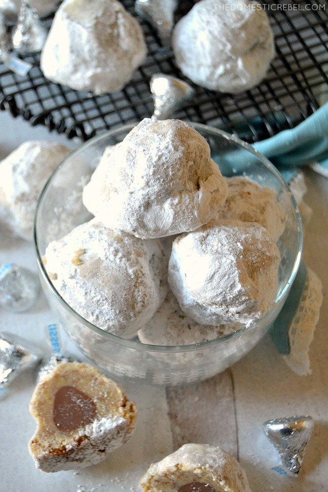 Snowball cookies piled in a clear bowl with candies