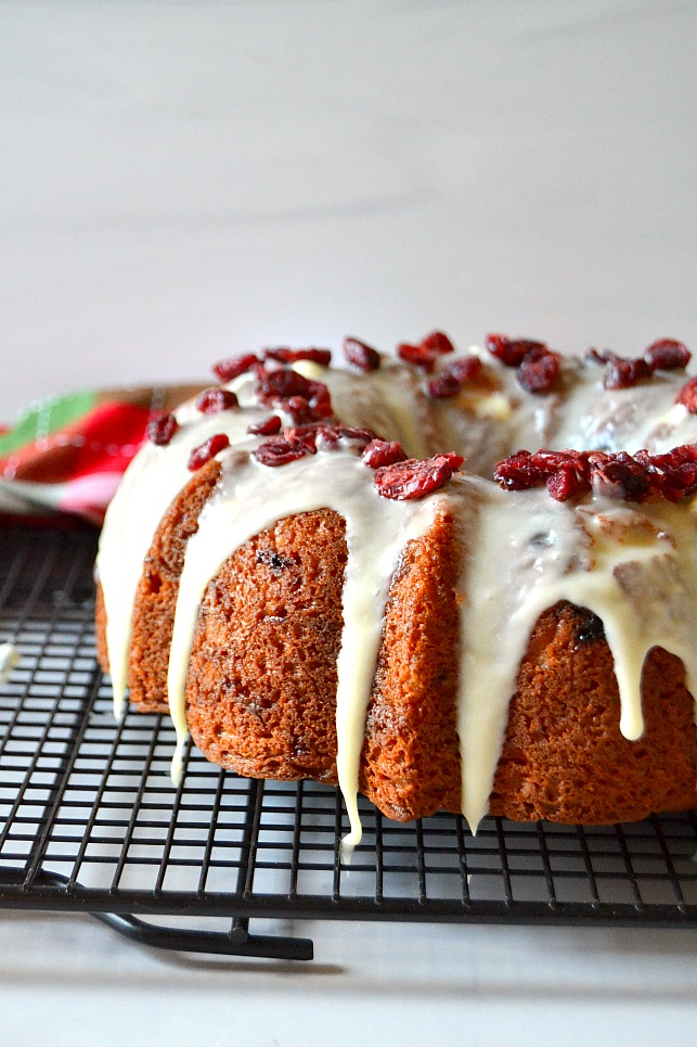 White chocolate cranberry bundt cake on a black wire rack