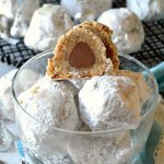 Snowball Kiss Cookies arranged in a clear plastic bowl