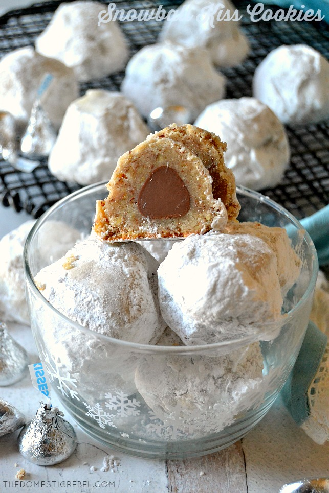 A cut open Snowball Kiss Cookie on top of cookies in a clear bowl