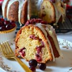 white chocolate cranberry bundt cake slice on white plate with gold fork