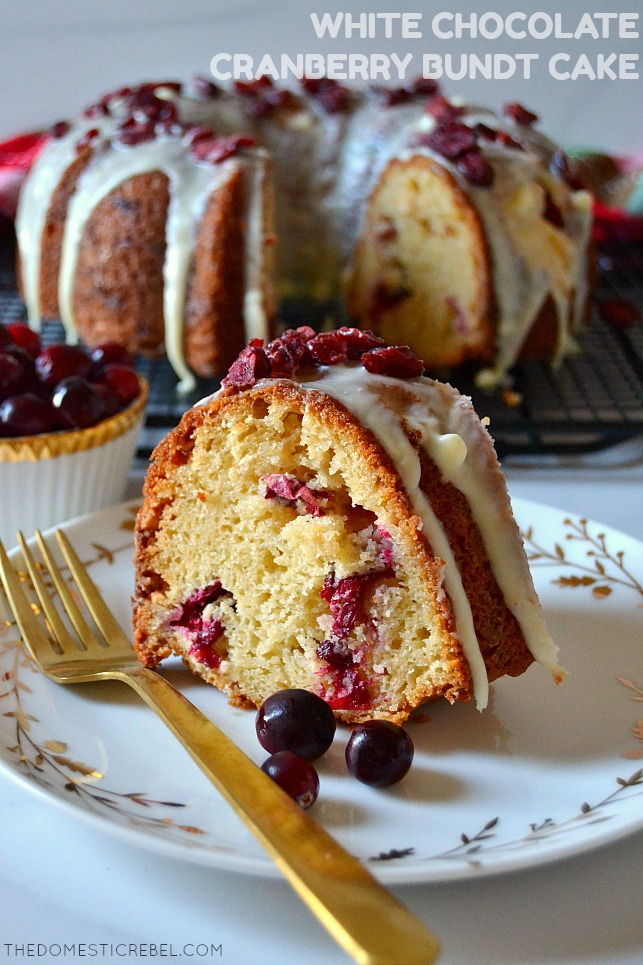 Slice of white chocolate cranberry bundt cake on a white and gold plate with a gold fork