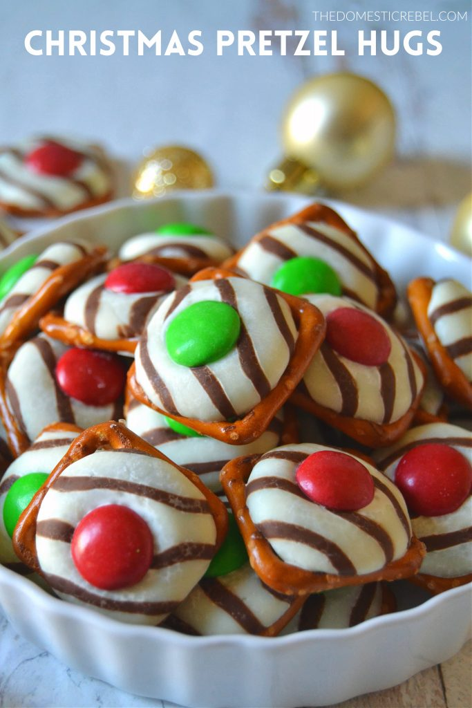 A white dish filled with Christmas pretzel hugs inside