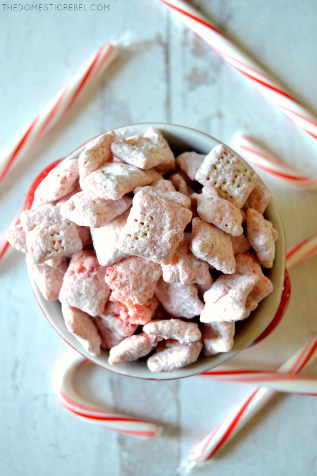Bowl of peppermint candy cane muddy buddies surrounded by candy canes