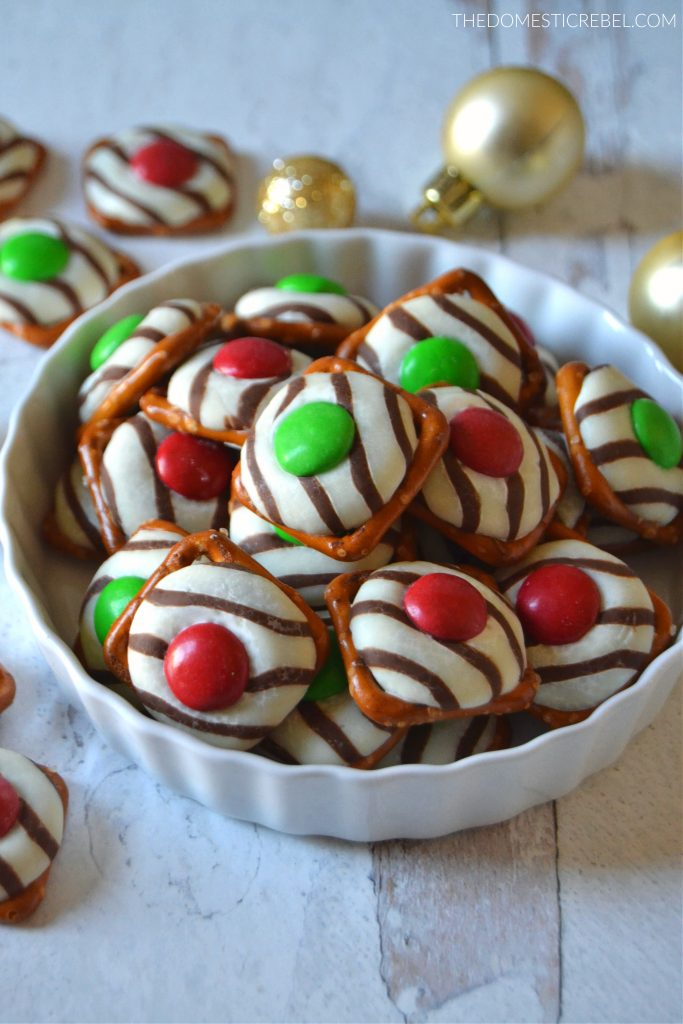 Christmas pretzel hugs in a white dish with gold ornaments