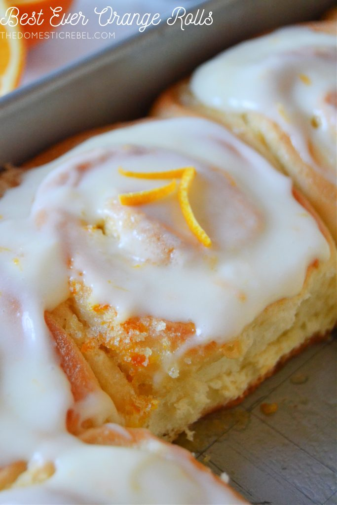 Closeup photo of an orange sweet roll in the pan with strips of orange zest