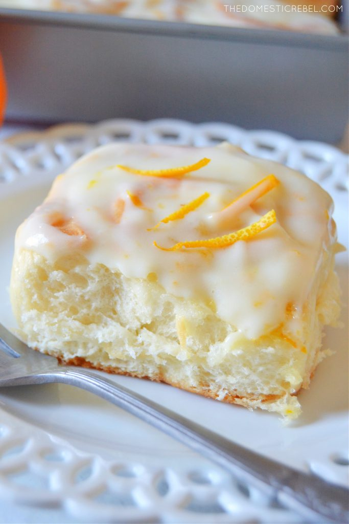 An orange sweet roll on a white lace plate with a silver fork