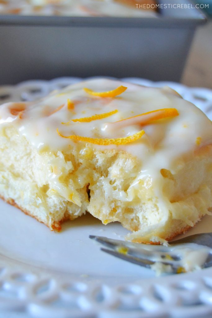 Orange sweet roll on a white lace plate with a fork